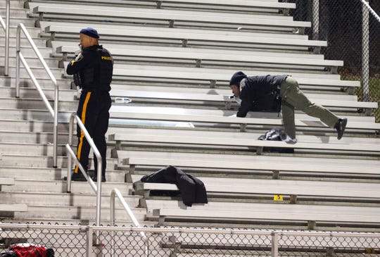 Pleasantville police search the stands after a shooting during a football game at Pleasantville High School in Pleasantville, N.J., Friday, Nov. 15, 2019.