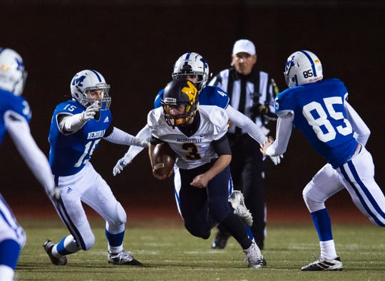 Mooresville's John Clampitt (3) breaks through Memorial's defense at the Mooresville vs Memorial game at Enlow Field in Evansville, Ind., Friday, Nov. 15, 2019. Memorial won 17-14 over Mooresville in the Class 4A regional. They will advance to semistate for the third straight season.