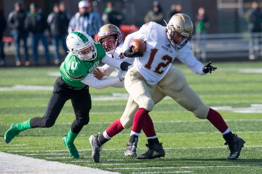 Dakx Lannert (12) escapes a tackle by Triton Central's Trent Walters (11) in Mater Dei's 13-7 loss in a Class 2A regional on Saturday.