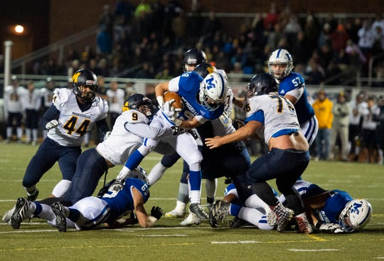 Memorial's Finn McCool (29) attempts to break through Mooresville's defense at the Mooresville vs Memorial game at Enlow Field in Evansville, Ind., Friday, Nov. 15, 2019.
