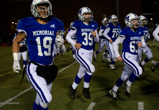 Memorial's Mason Auker (19), Louis Seward (39), and Dalton Shaw (63) run onto the field before playing Mooresville at Enlow Field in Evansville, Ind., Friday, Nov. 15, 2019.