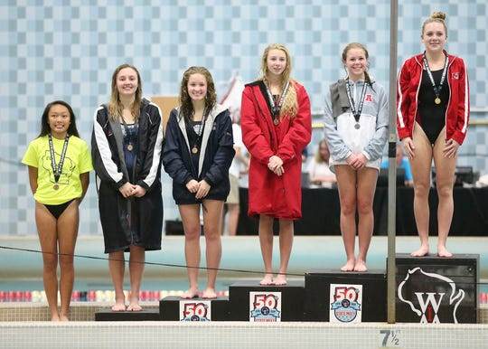 Appleton West/Kimberly High School's Abby Hopfensperger (second from left) is awarded 5th place, while Neenah's Bailey Schroeder and Av Osero (third from right and far right ) are awarded third and first Saturday, November 16, 2019 in the Division 1 WIAA state diving meet in Madison Wis.