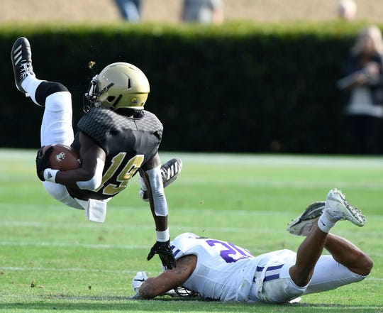Furman's Darius Kearse (2) upends Wofford's Jacquez Allen (19).