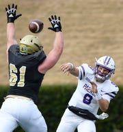 Furman quarterback Hamp Sisson (9) gets off a pass under pressure from Wofford's Austin Lufkin (61).