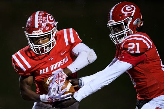 Greenville's Tennelle Franklin (21) hands the ball to Khalique Holland (2) during their game against BHP Friday, Nov. 15, 2019.