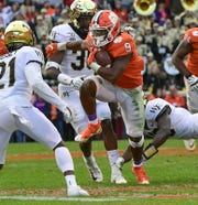 Clemson running back Travis Etienne (9) runs near Wake Forest defensive back Essang Bassey(21) during the second quarter at Memorial Stadium in Clemson, South Carolina Saturday, November 16, 2019.