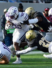 Furman's Devin Abrams (32) digs for yards with Wofford defenders in tow.