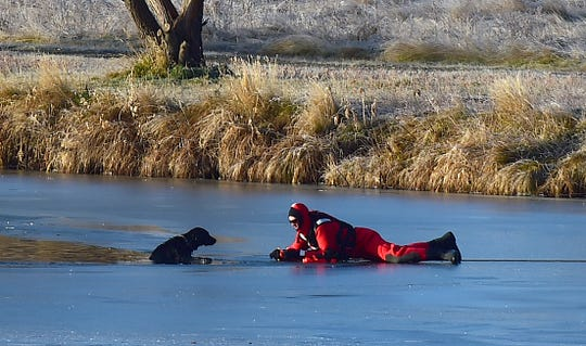 Billings firefighter Lee Fischer crawls onto thin ice in a dry suit as he rescues a black Labrador dog that fell through the ice at Lake Elmo State Park, Thursday, Nov. 14, 2019, in n Billings. Mont. (Larry Mayer/The Billings Gazette via AP)