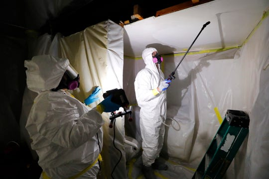 File - In this Oct. 18, 2017, file photo, Asbestos Removal Technologies Inc., job superintendent Ryan Laitila, right, sprays amended water as job forman Megan Eberhart holds a light during asbestos abatement in Howell, Mich. A federal appeals court says the Trump administration unlawfully excluded millions of tons of some of the most dangerous materials in public use from a safety review. (AP Photo/Paul Sancya, File)