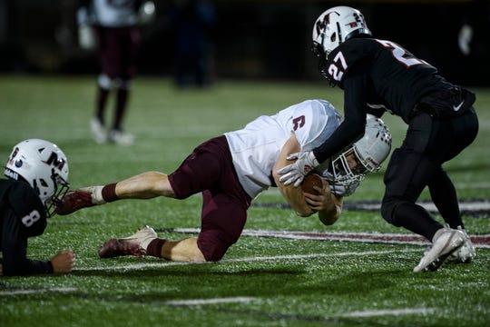 Henderson County's Logan Green (6) advances the ball before being taken down by McCracken County's Ian McCune (8) and McCracken County's Colton Crowell (27) during a second round playoff game at Marquette Stadium in Paducah, Ky., Friday, Nov. 15, 2019.