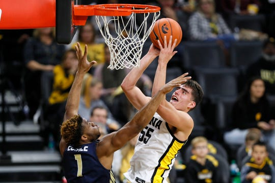 Iowa center Luka Garza (55) drives to the basket over Oral Roberts forward Elijah Lufile during the second half Friday. Garza finished with a career-high 30 points.