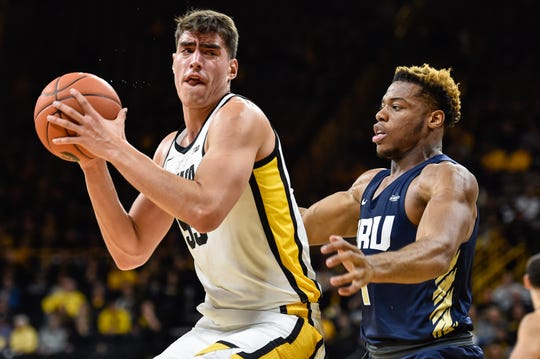 Iowa center Luka Garza controls the ball as Oral Roberts forward Elijah Lufile defends during the first half at Carver-Hawkeye Arena on Friday.