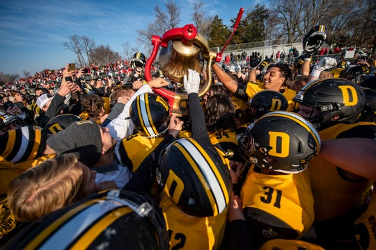 DePauw players hoist the bell over their heads as they celebrate winning the Monon Bell Game, Saturday, Nov. 16, 2019, in Greencastle, Ind. DePauw won the game 17-13 to take the Monon Bell from Wabash.