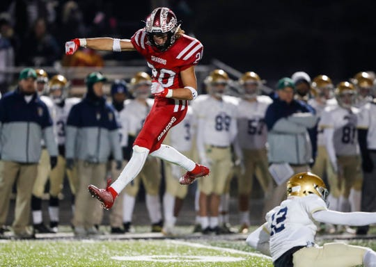 New Palestine strong safety Maxen Hook (20) jumps in the air after tackling Cathedral quarterback Orin Edwards (12) Friday, Nov. 15, 2019, at New Palestine High School, New Palestine, Ind. The Dragons defeated Cathedral, 35-10, for the Class 5A regional championship.