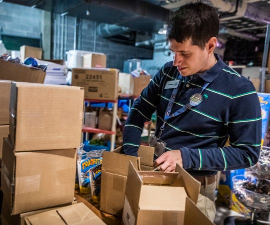 Andrew Van Cleave processes items for the gift shop while volunteering at the Adventure Science Center on Nov. 7, 2019.