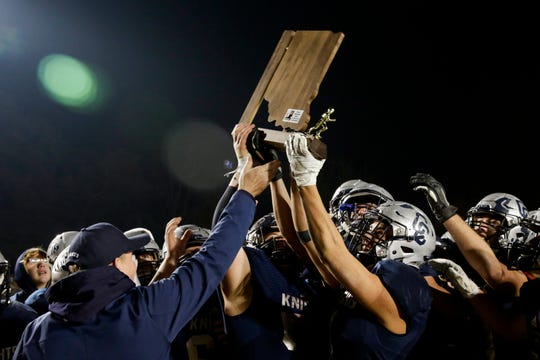 Central Catholic athletic director Tim Bordenet presents the championship trophy to the Knights, who defeated North Judson 43-17 to win the IHSAA Class A regional title, Friday, Nov. 15, 2019 in Lafayette