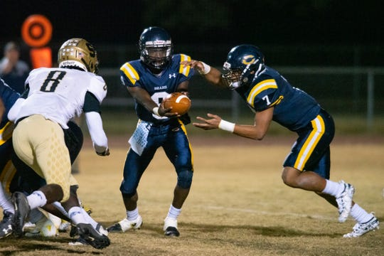 Carencro high's Tavion Faulk (9) hands off the ball to Kendrell Williams (7) as the Carencro High Golden Bears take on the Salmen High Spartans at Carencro Friday, Nov. 15, 2019.