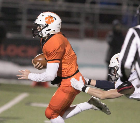 Quarterback Colby Newburg eludes a tackle while running 34 yards for Brighton's first touchdown in a 35-20 victory over Hudsonville on Friday, Nov. 15, 2019.