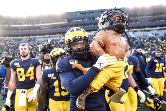 Michigan's Devin Gill carries the Paul Bunyan Trophy after the game on Saturday, Nov. 16, 2019, at Michigan Stadium in Ann Arbor. Michigan beat Michigan State 44-10.