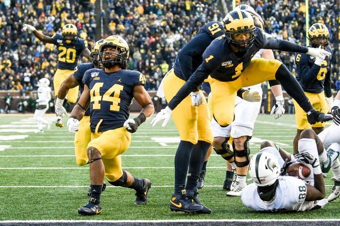Michigan's defense, including Cameron McGrone, left, and Ambry Thomas, right, celebrate after stopping the Spartans on fourth down late during the fourth quarter on Saturday, Nov. 16, 2019, at Michigan Stadium in Ann Arbor.