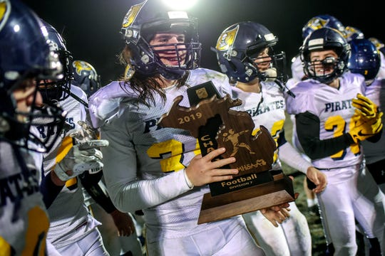 Pewamo-Westphalia's Carter Thelen holds the trophy while the Pirates celebrates after winning the Division 7 championship on Friday, Nov. 15, 2019, at New Lothrop High School.