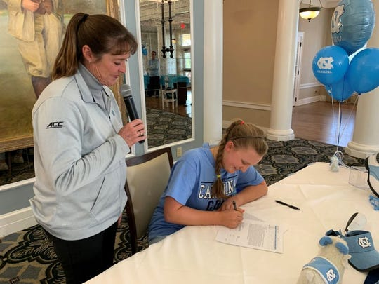 Former LPGA champion Donna Andrews   watches as Nicole Adam signs her national letter of intent to attend North Carolina. Andrews is a UNC alum