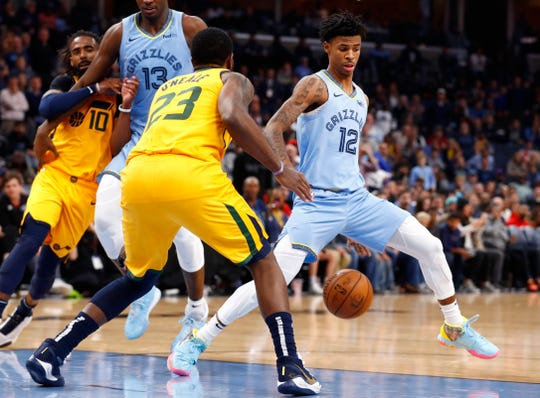 Memphis Grizzlies guard Ja Morant dribbles in between his legs on a drve as Utah Jazz forward Royce O'Neale dfends during their game at the FedExForum on Friday, Nov. 15, 2019.