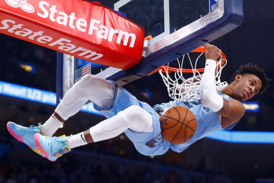 Memphis Grizzlies guard Ja Morant hangs on the rim after a dunk against the Utah Jazz during their game at the FedExForum on Friday, Nov. 15, 2019.