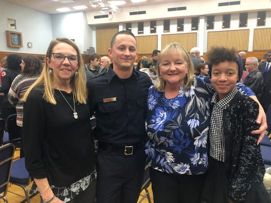 Sean Gelles, a new Milwaukee firefighter, is seen at his graduation ceremony Thursday after receiving a pair of cuff links the department awarded to his grandfather. From left, Annette Wagner, his aunt; Gelles; Linda Gelles, his mother; and Amaya Spicuzza, a family friend.