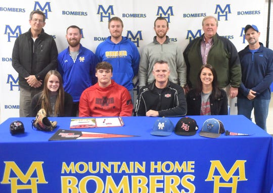 Mountain Home pitcher/infielder Will Gross (front, second from left) signed a National Letter of Intent on Friday to play college baseball at Arkansas State University. Pictured with Gross are: (front row) his sister Gaby Gross, his father Lance Gross, his mother Kerri Gross; (back row) MHHS assistant Phillip Taylor, MHHS assistant Blake Hendricks, MHHS assistant Kyle Stephens, MHHS head coach Tim Carver, and Gross's youth coaches Tom Jordan and Jerry Prinner.
