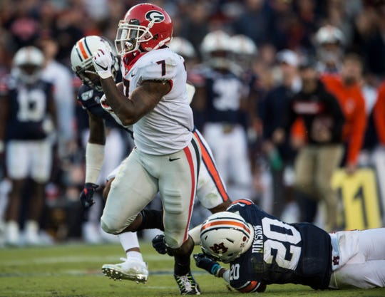 Georgia running back D'Andre Swift (7) is tripped up by Auburn defensive back Jeremiah Dinson (20) after breaking a long run at Jordan-Hare Stadium in Auburn, Ala., on Saturday, Nov. 16, 2019. Georgia leads Auburn 14-0 at halftime.