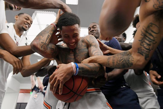 Auburn guard J'Von McCormick (5) gets the game ball and celebrates with his teammates after a win over CSUN on Nov. 15, 2019 in Auburn, Ala.