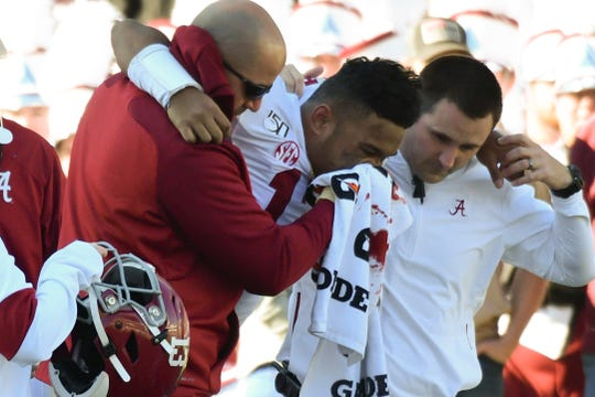 Nov 16, 2019; Starkville, MS, USA; Alabama Crimson Tide quarterback Tua Tagovailoa (13) assisted by team personnel after an injury during the second quarter of the game against the Mississippi State Bulldogs at Davis Wade Stadium. Mandatory Credit: Matt Bush-USA TODAY Sports