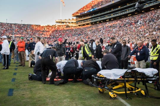 A photographer is helped off the field after being hit by a player at Jordan-Hare Stadium in Auburn, Ala., on Saturday, Nov. 16, 2019. Georgia leads Auburn 14-0 at halftime.