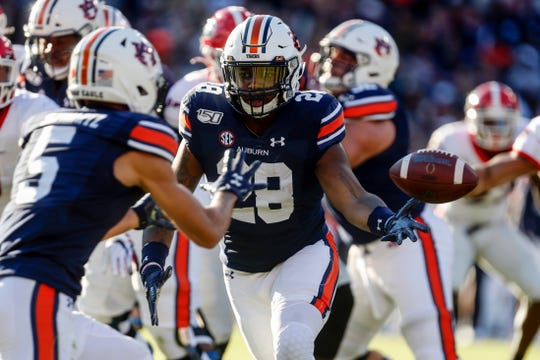 Auburn running back JaTarvious Whitlow (28) flips the ball to Auburn wide receiver Anthony Schwartz (5) on a reverse during the first half of an NCAA college football game against Georgia, Saturday, Nov. 16, 2019, in Auburn, Ala. (AP Photo/Butch Dill)