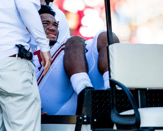 Alabama quarterback Tua Tagovailoa is helped off the field after being injured against Mississippi State on Saturday.