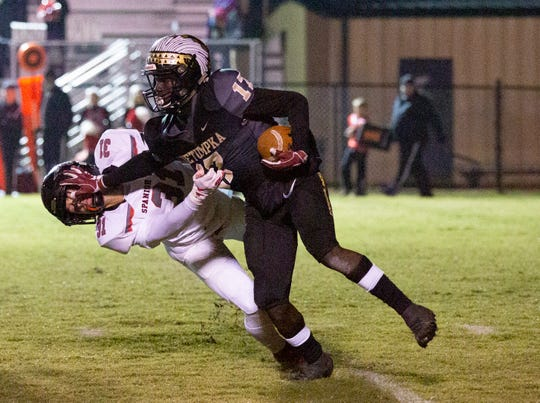 Wetumpka's Brandon Bowman tries to fend off a tackle from Spanish Fort's Trent Hays.