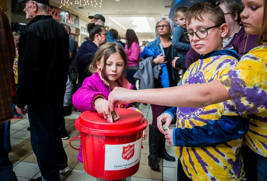 Attendees drop money in a red kettle during the Salvation Army's 2019 Red Kettle Campaign Kickoff at the Muncie Mall.