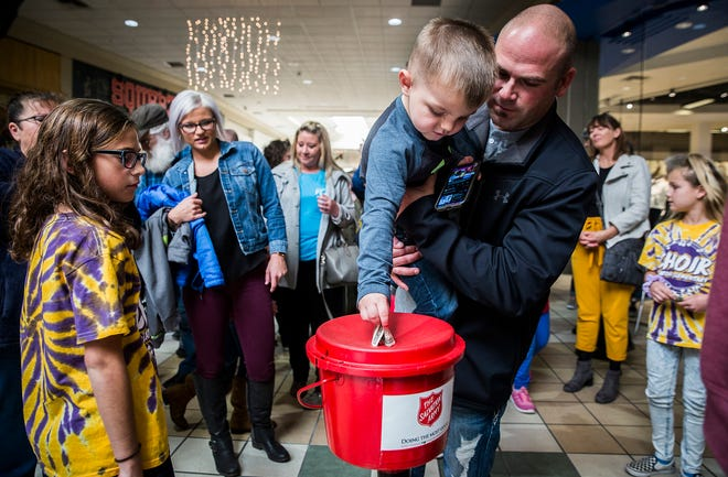 Attendees drop money in a red kettle during the Salvation Army's Red Kettle Campaign Kickoff at the Muncie Mall in 2019.