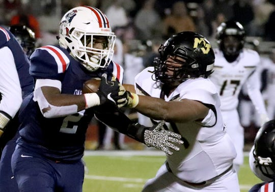 Oakland's Jordan Brown (2) runs the ball  as Mt. Juliet's defensive lineman Derek Miller (34) moves in for a tackle during the second round of the High School Football playoffs, on Friday, Nov. 15, 2019, at Oakland.