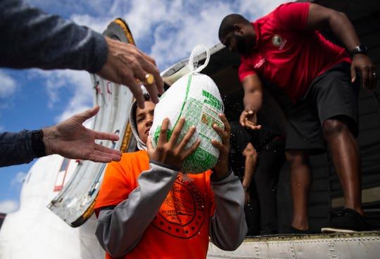 Darin Donalds, 12, center, takes over a frozen turkey from Byron Donalds, right, and passes it to pilot Tom Powers during the 7th annual Turkeys Take Flight on Saturday, November 16, 2019, at Immokalee Regional Airport.