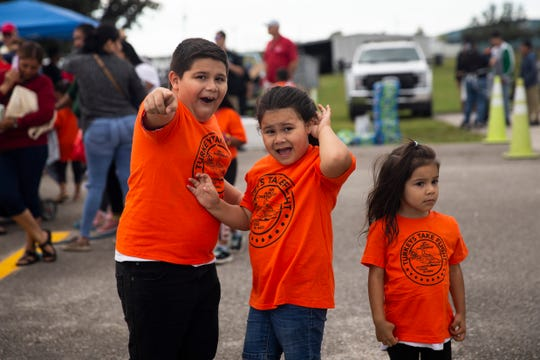 From left to right, Josue Hernandez, 8, Reyna Hernandez, 5, and Nayeli Hernandez, 3, cheer as the aircraft lands at Immokalee Regional Airport on Saturday, November 16, 2019.