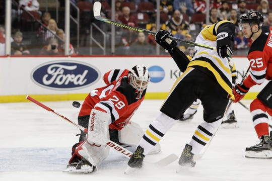 New Jersey Devils goaltender Mackenzie Blackwood (29) stops a shot by Pittsburgh Penguins' Nick Bjugstad (27) during the first period of an NHL hockey game Friday, Nov. 15, 2019, in Newark, N.J.