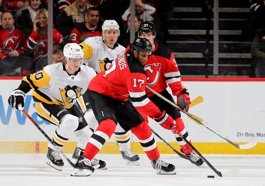 Wayne Simmonds #17 of the New Jersey Devils takes the puck as Juuso Riikola #50 of the Pittsburgh Penguins defends in the first period at Prudential Center on Nov. 15, 2019 in Newark, N.J.