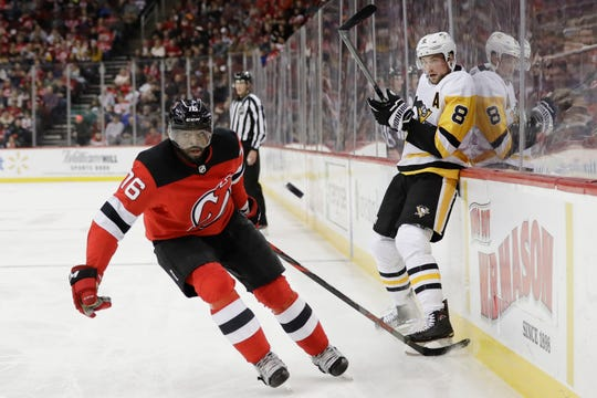 Pittsburgh Penguins' Brian Dumoulin (8) passes the puck away from New Jersey Devils' P.K. Subban (76) during the first period of an NHL hockey game Friday, Nov. 15, 2019, in Newark, N.J.
