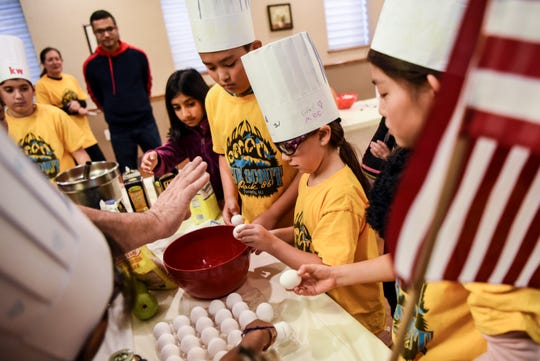 Local scouts learn to cook Thanksgiving treats to benefit Merlin's Kids, a non profit organization dedicated to providing individually trained service dogs to those in need. Shown at the American Legion in Cresskill  on Saturday November 16, 2019. Giza Miller Pringle, 7 gets a lesson in how to properly crack an egg.