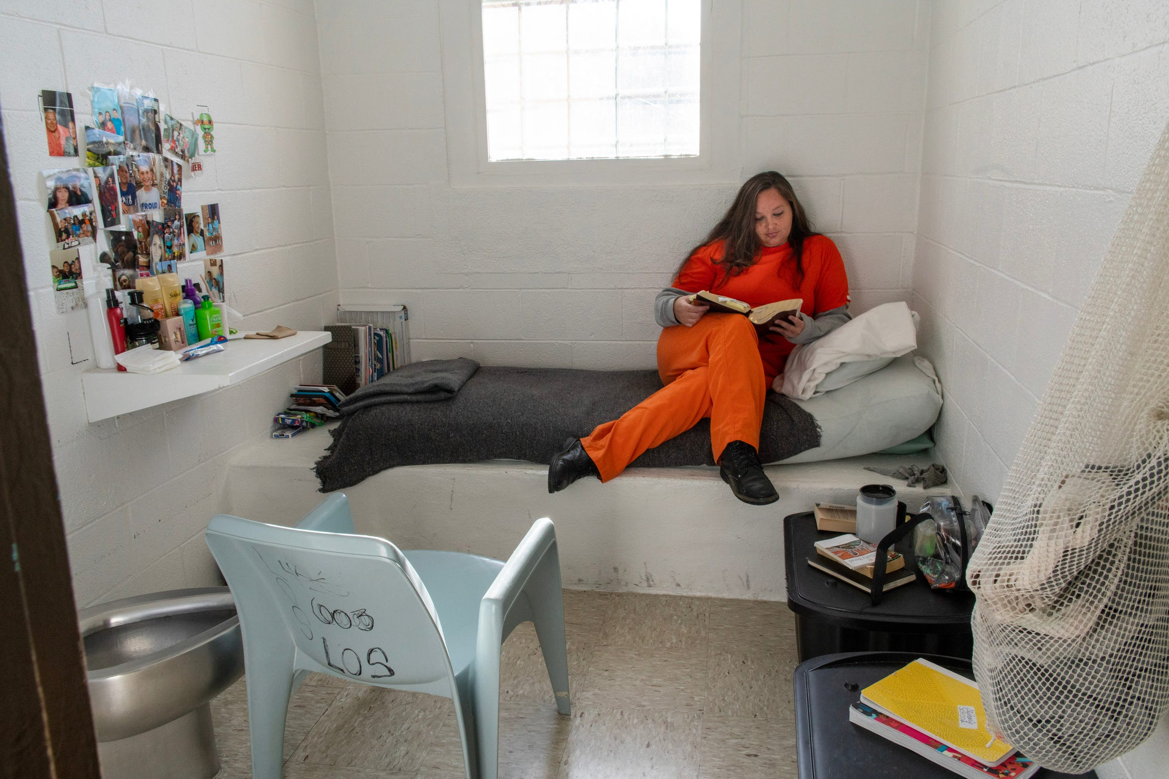 Stephanie Baker reading in her cell in the Springer Correctional Center in Springer. She was housed in the low security section of the prison, where inmates have private quarters.