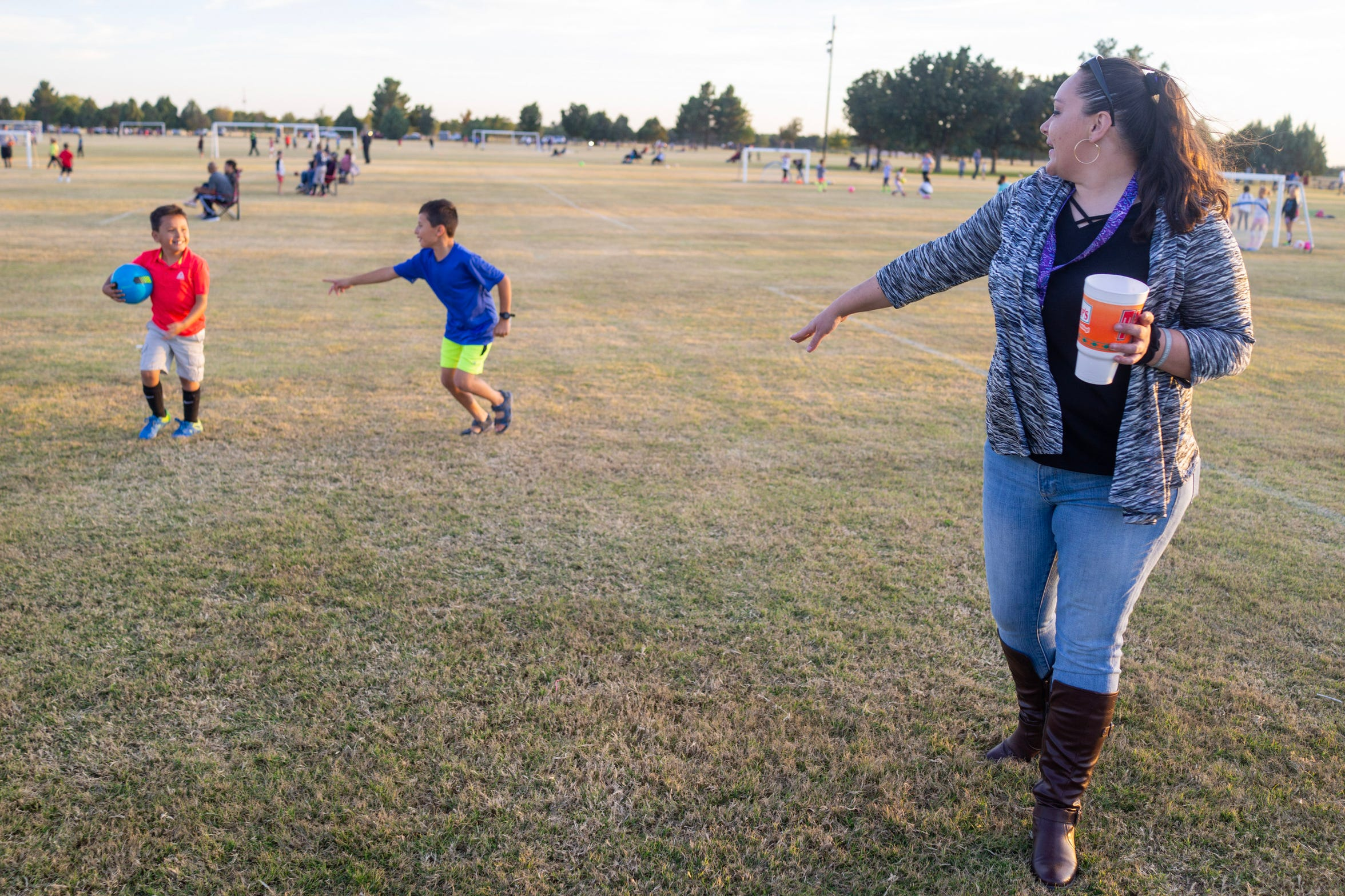Stephanie Baker keeping an eye on her sons Haydnn and Jacob as they romp after thier practice at the soccer fields in Roswell.