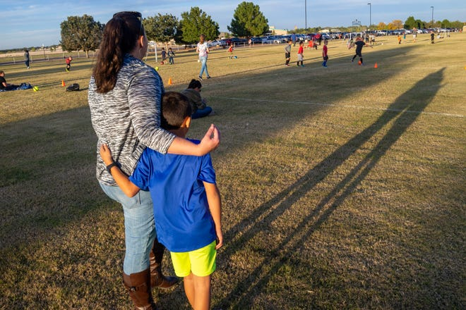 Stephanie Baker and her middle son watch his brothers play at the soccer fields in Roswell. She takes the boys to soccer during her weekend visits with them. Once she has rebuilt her relationship with the boys, she plans to assume custody from her grandparents.