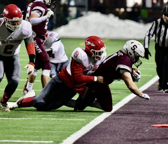 Port Huron defensive player Malik Davis tackles Seaholm running back Will McBride in the end zone